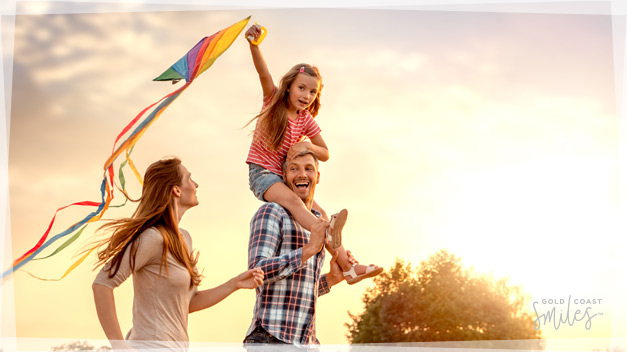 A happy family running with a colourful kite