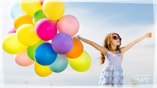 Happy young girl smiling and holding colourful balloons