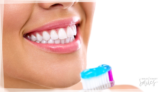 A women with a white bright smile about to brush her teeth