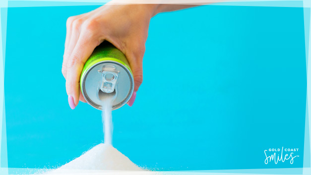 A ladies hand pouring sugar out of a soda can