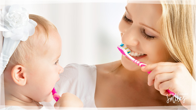 A smiling women teaching her baby girl how to brush her teeth