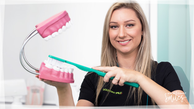 Dental Assistant Maggie, holding a large teeth model and large Toothbrush