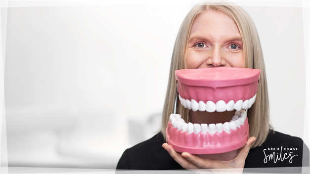 Practice Manager Karen, holding a large teeth model